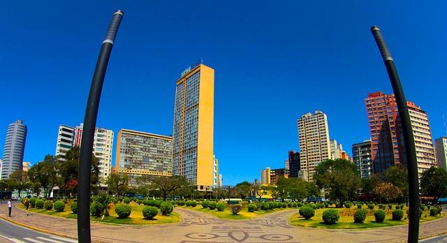 Praça Raul Soares, com grama e jardins em tons de verde, com edifício de paredes amarelas, prédios ao redor e céu azul de inverno no Brasil