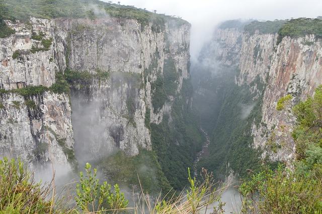 Paredões rochosos, com vegetação verde escura subindo. Há neblina, pois a foto foi tirada durante o inverno no Brasil