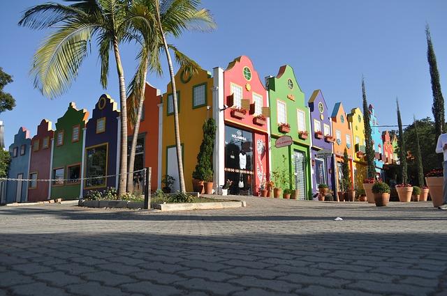 Casas com fachadas coloridas em tons de vermelho, verde, roxo, laranja, amarelo e azul. Na frente, palmeiras.
